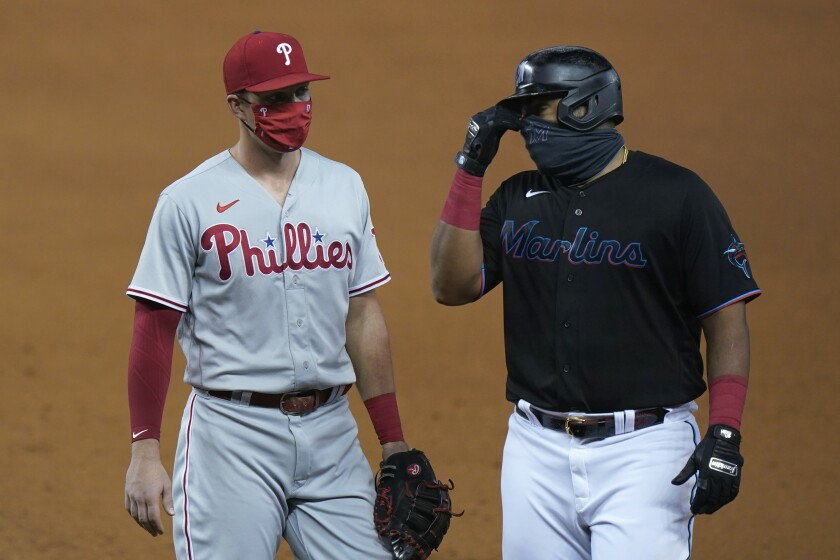 Phillies first baseman Rhys Hoskins talks with Miami's Jesus Aguilar during a game on Sept. 12 in Miami.