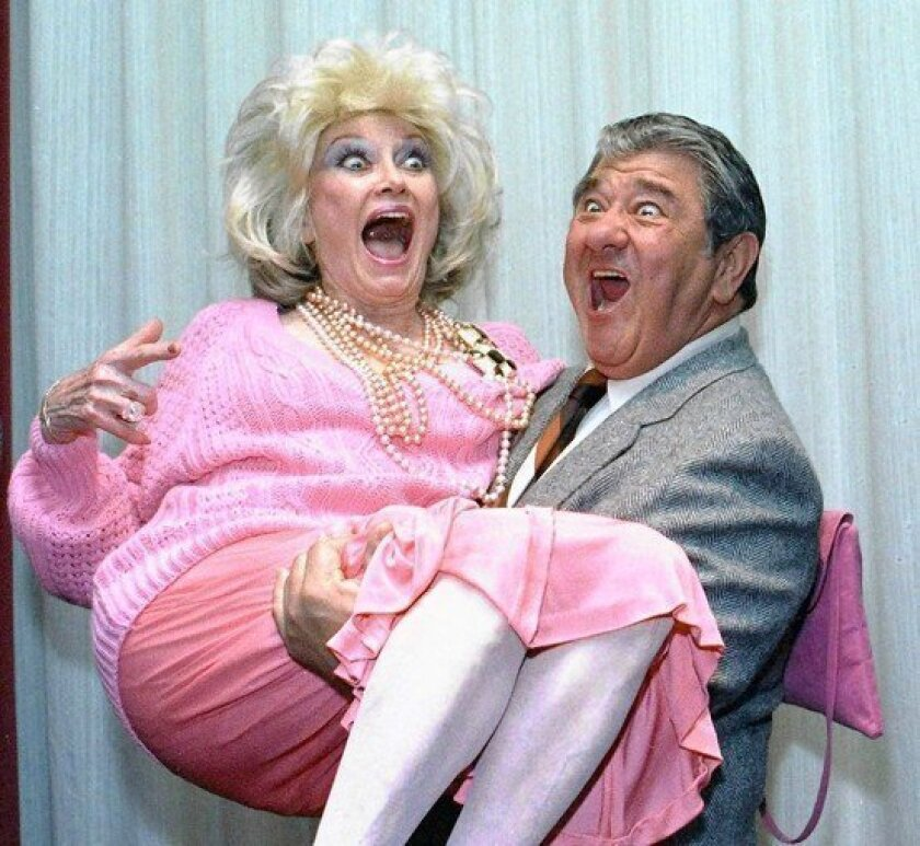 Comedian Phyllis Diller gets a lift from Buddy Hackett in 1985.
