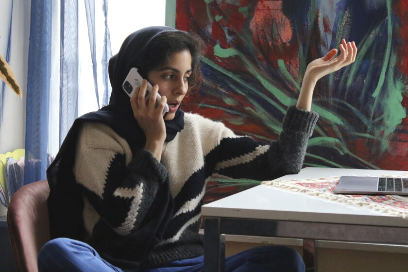 Iranian American activist Hoda Katebi, 24, speaks to another activist on Jan. 12, 2020 in her Chicago apartment. She and her network had received word that morning that an Iranian student was being detained at O'Hare International Airport. (AP Photo/Noreen Nasir)