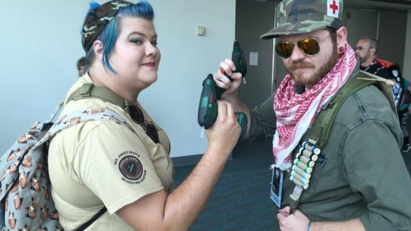 """Cosplay repair """"heroes"""" Caitlin Brown, 28, and Todd Kimmell, 31, make the rounds at San Diego's Comic-Con as visitors hail them for some quick costume repairs. (/ Luis Gomez)"""