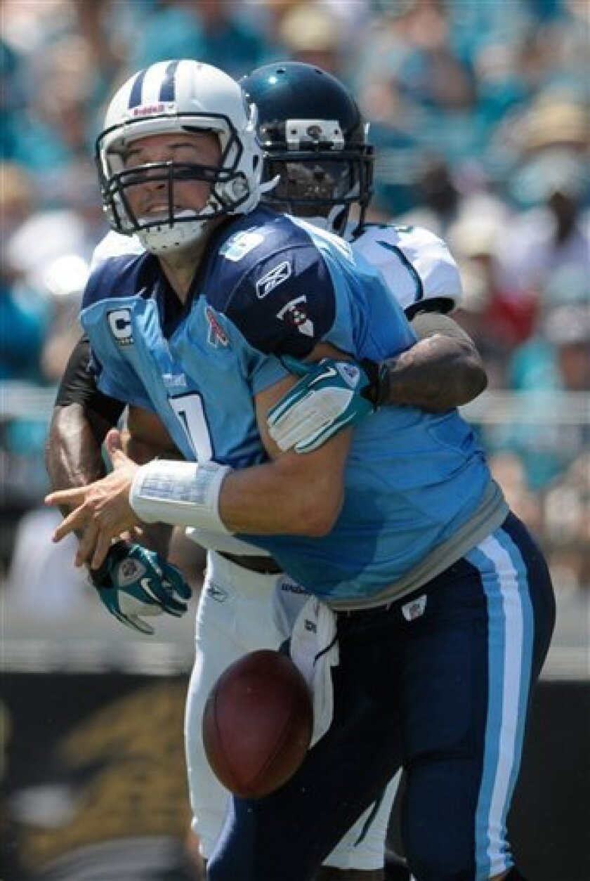 Tennessee Titans quarterback Matt Hasselbeck (8) fumbles the ball as he is sacked by Jacksonville Jaguars defensive back Drew Coleman, rear, during the first half of an NFL football game in Jacksonville, Fla., Sunday, Sept. 11, 2011. (AP Photo/Phelan Ebenhack)