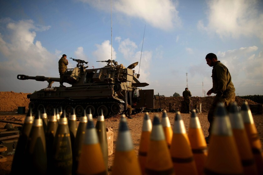 Soldiers in an Israeli artillery unit take positions Monday near the Gaza border.