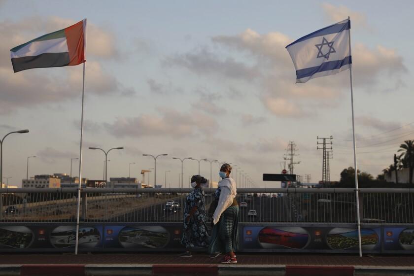 Women walk past United Arab Emirates and Israeli flags