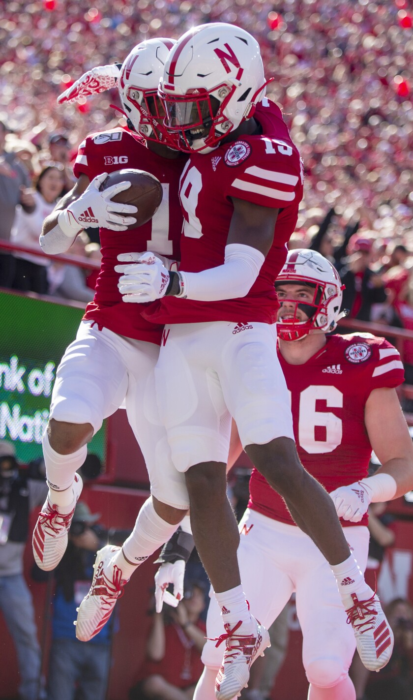 Nebraska wide receiver Wan'Dale Robinson, left, and safety Marquel Dismuke (19) jump in the air in celebration of Robinson's touchdown run during an NCAA college football game against Northwestern, Saturday, Oct. 5, 2019 in Lincoln, Neb. (Emily Haney/Lincoln Journal Star via AP)