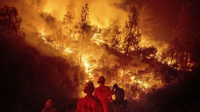 FILE - In this Aug. 7, 2018 file photo, firefighters monitor a backfire while battling the Ranch Fir