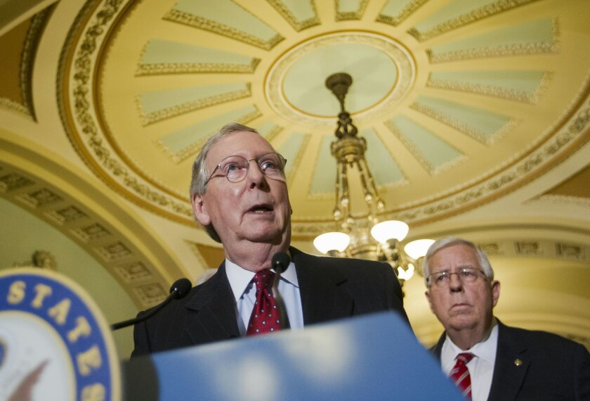 FILE - Senate Majority Leader Mitch McConnell of Ky., accompanied by Sen. Mike Enzi, R-Wyo., speaks to reporters on Capitol Hill in Washington, in this March 24, 2015 file photo. Senators worked into Friday's pre-dawn hours March 27, 2015 on a stack of amendments to the balanced-budget plan, which