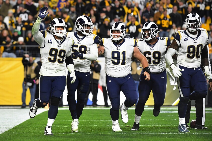 Aaron Donald (99) celebrates with the Rams defense after sacking Steelers quarterback Mason Rudolph in the end zone for a safety during a game Nov. 19.