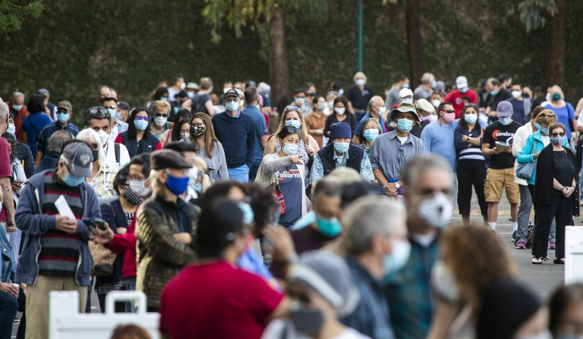 Healthcare workers wait in line to receive the COVID-19 vaccine at the Disneyland Resort in Anaheim.