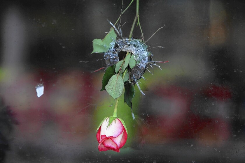 Flowers hang in a bullet hole in the window of the I.V. Deli Mart in Isla Vista, Calif.