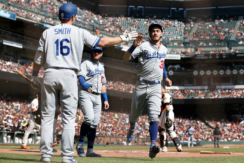 Dodgers teammates Cody Bellinger, right, and Max Muncy, center, celebrate.