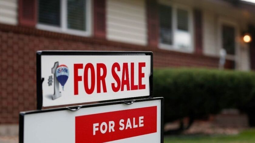 A for sale sign stands outside a home on the market on Oct. 2, 2018, in the north Denver suburb of Thornton, Colo. According to the latest data released Nov. 8 by Freddie Mac, the 30-year fixed-rate average jumped to 4.94 percent with an average 0.5 point.