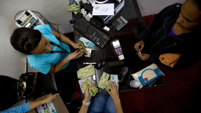 """A customer buys bank notes called """"Panales"""" at a comunal bank in the 23 de Enero neighborhood of Car"""