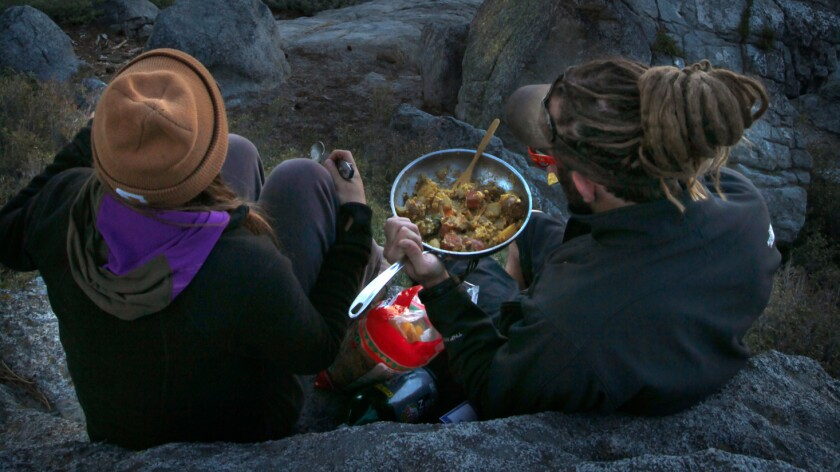 Two visitors enjoy a hot skillet of eggs, potatoes and vegetables, and a front-row seat to view Half Dome, at Washburn Point.