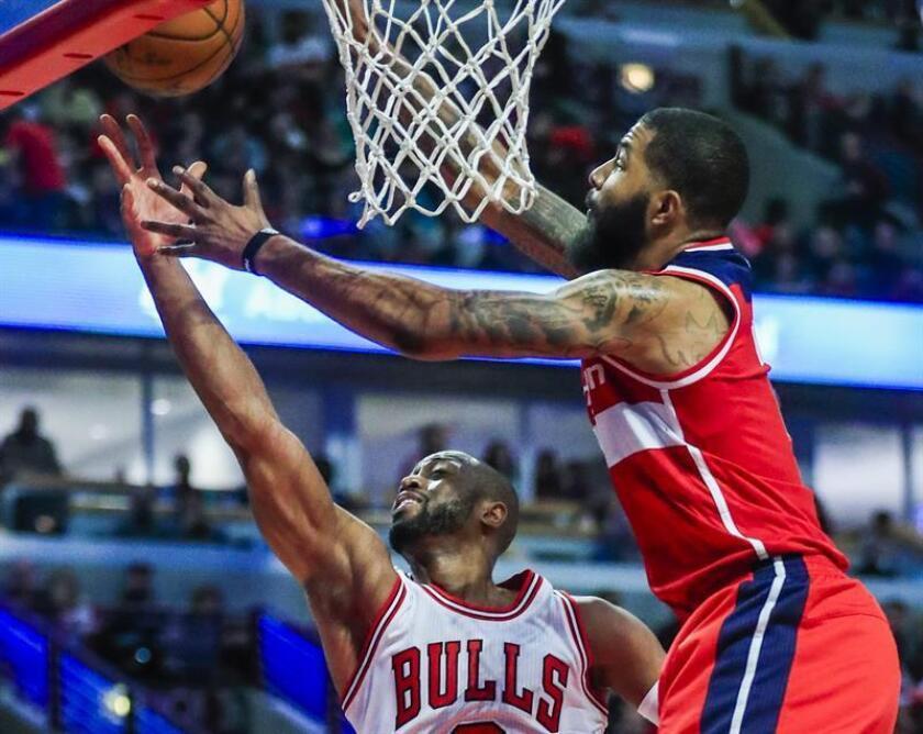 Dwyane Wade (i) de Chicago Bulls salta para encestar contra Markieff Morris (d) de Washington Wizards en un juego de la NBA en United Center en Chicago (EE.UU.). EFE/Archivo