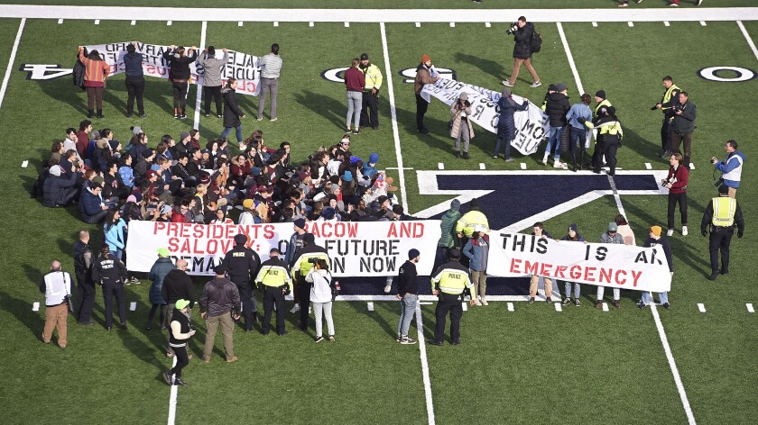 Demonstrators stage a climate change protest Nov. 23 at the Yale Bowl, delaying the start of the second half of an NCAA college football game between Harvard and Yale.