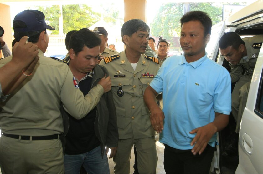 Chay Sarith, second left, and Mao Hoeun, second right in light blue shirt, suspected attackers who are accused of beating two opposition lawmakers along with another  man, are escorted by police officers at Phnom Penh Municipal Court in Phnom Penh, Cambodia, Wednesday, Nov. 4, 2015. Three suspects