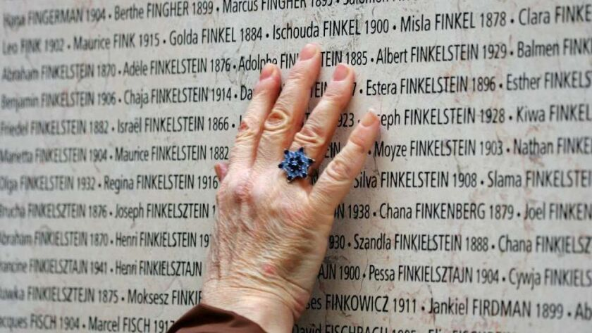 A hand touches the Wall of Names at a Sh