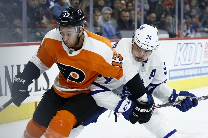 Philadelphia Flyers' Kevin Hayes (13) and Toronto Maple Leafs' Auston Matthews (34) battle for position during the third period of an NHL hockey game, Tuesday, Dec. 3, 2019, in Philadelphia. (AP Photo/Matt Slocum)