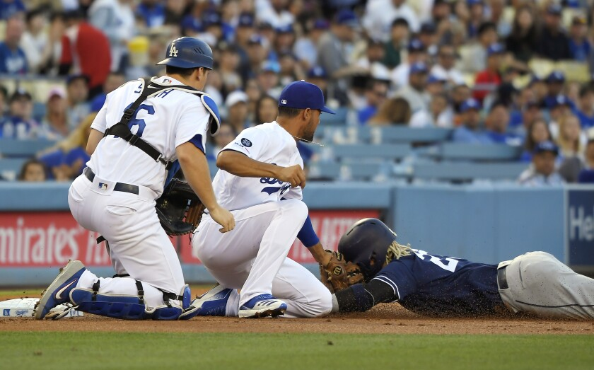 The Padres' Fernando Tatis Jr. is tagged out by Los Angeles Dodgers shortstop Kristopher Negron as catcher Will Smith backs up the play in the first inning.