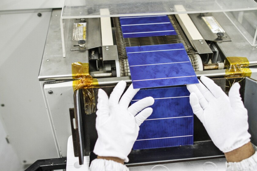 Edison International acquired Chicago-based solar developer SoCore Energy, which installs and operates solar panels for retail and commercial clients. Above is an example of a solar panel being manufactured.