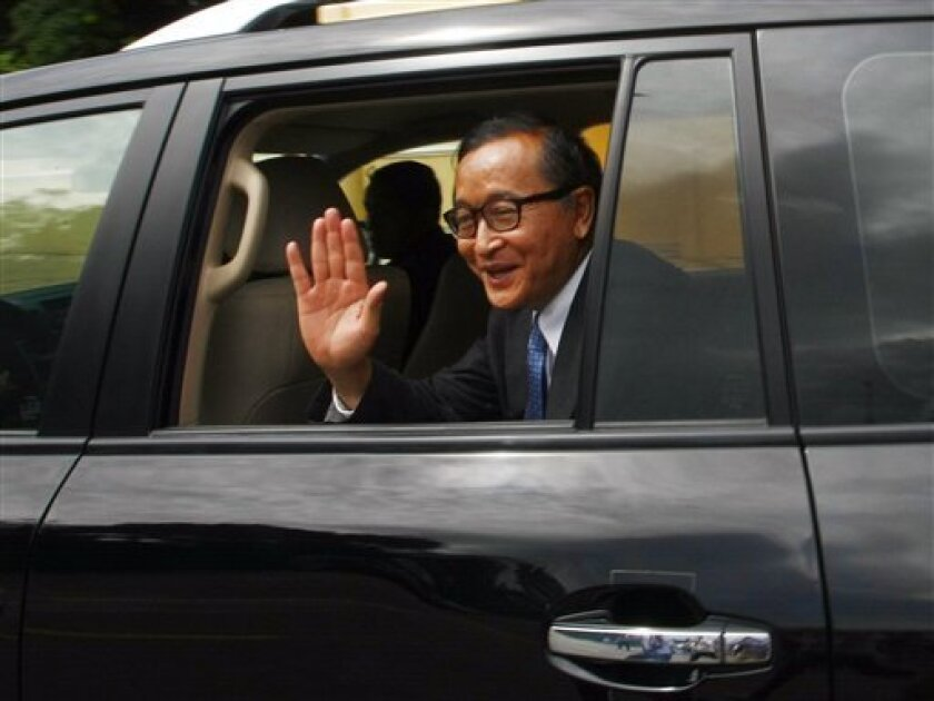 Cambodia's opposition leader Sam Rainsy waves from his car after a meeting in Phnom Penh, Cambodia, Saturday, Sept. 14, 2013. Cambodia's long-ruling Prime Minister Hun Sen briefly met the head of main opposition party for the first time in years Saturday, but the two rivals reached no agreement on how to end the political stalemate that has simmered since the country's disputed election. (AP Photo/Heng Sinith)
