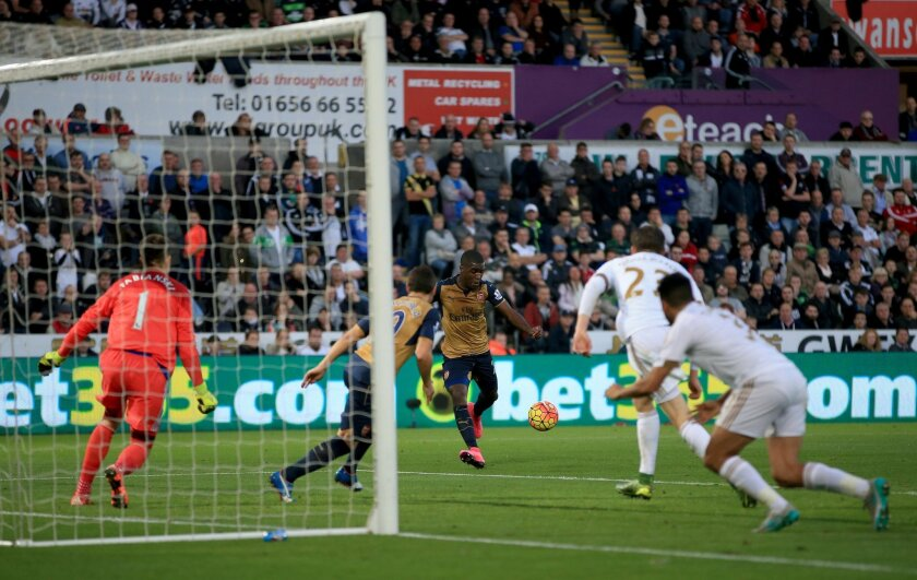 Arsenal's Joel Campbell, center, scores his side's third goal of the game during their English Premier League soccer match against Swansea City at the Liberty Stadium, Swansea, Wales, Saturday, Oct. 31, 2015. (Nick Potts/PA via AP)    UNITED KINGDOM OUT      -     NO SALES      -    NO ARCHIVES