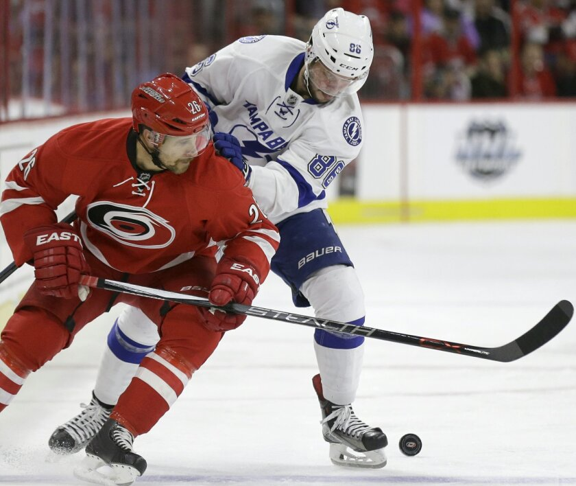 Carolina Hurricanes' John-Michael Liles, left, and Tampa Bay Lightning's Nikita Kucherov (86), of Russia, skate for possession of the puck during the first period of an NHL hockey game in Raleigh, N.C., Sunday, Nov. 1, 2015. (AP Photo/Gerry Broome)