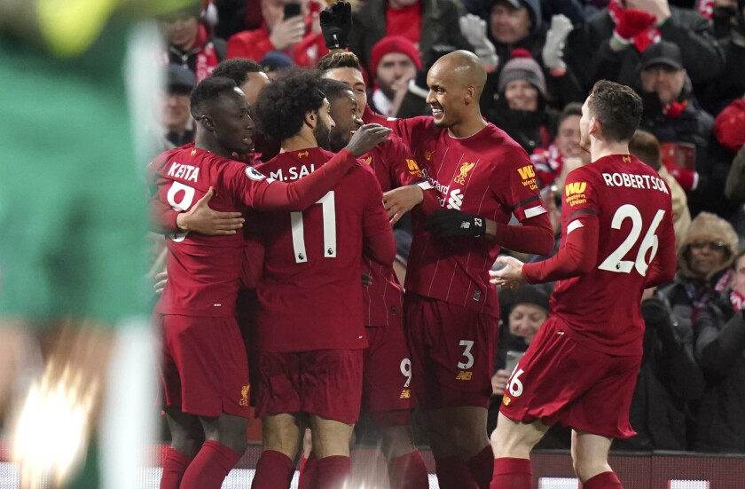 Liverpool players celebrate their goal during the English Premier League soccer match between Liverpool and West Ham in Liverpool, England on Monday.