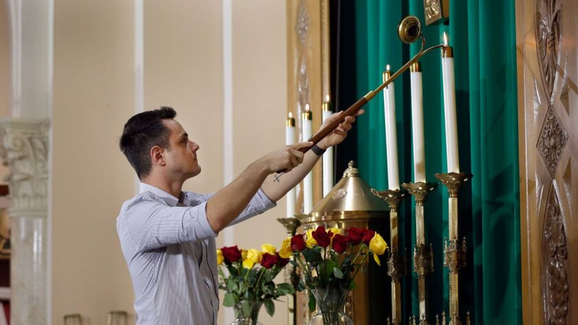 """Richard Peterson lights altar candles prior to an """"Always Our Children"""" mass Saturday at St. John th"""