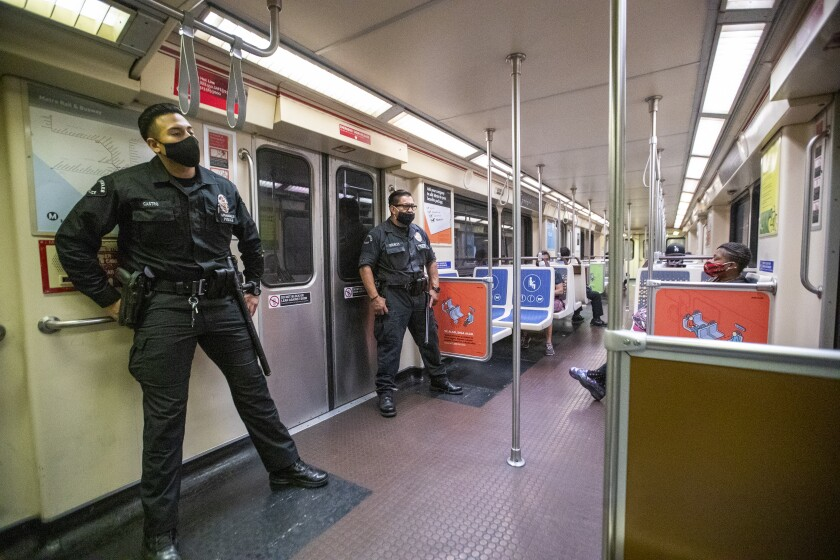 Two LAPD officers patrol a Metro Red Line subway car.