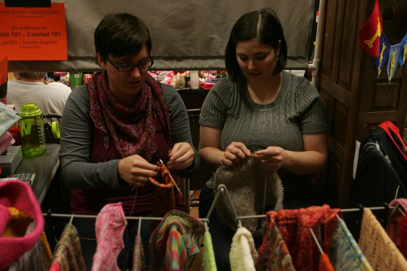 Helena Bristow (left) and Sara Hodges knit as they sell their craft at last year's Craft Mafia Holiday Hit List show in North Park.