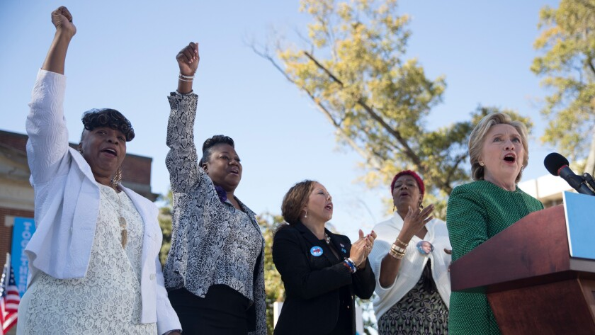 Gwen Carr, mother of Eric Garner; Sybrina Fulton, mother of Trayvon Martin; Lucia McBath, mother of Jordan Davis; and Maria Hamilton, mother of Dontre Hamilton, cheer while Hillary Clinton speaks on Sunday in Raleigh.