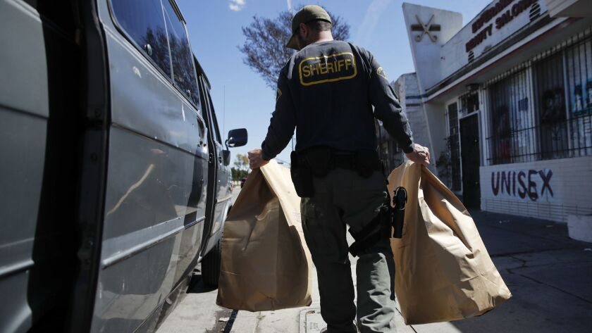 An undercover Los Angeles County sheriff's deputy loads two evidence bags into a van after raiding an illegal marijuana dispensary in Compton in 2018.