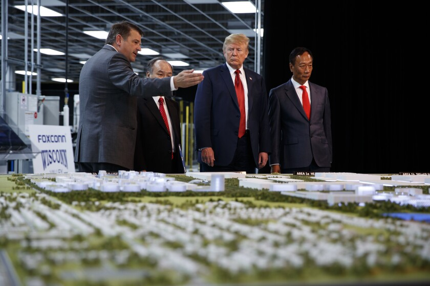 FILE - In this June 28, 2018 photo, President Donald Trump takes a tour of Foxconn with Foxconn chairman Terry Gou, right, and CEO of SoftBank Masayoshi Son in Mt. Pleasant, Wis. Foxconn Technology Group, the world's largest electronics manufacturer, has reached a new deal with reduced tax breaks for its scaled back project in southeast Wisconsin, Gov. Tony Evers and the the company announced on Monday, April 19, 2021. (AP Photo/Evan Vucci, File)