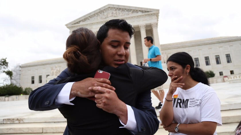 Immigration supporters react outside the U.S. Supreme Court after the justices issued a split ruling on President Obama's immigration policy Thursday.