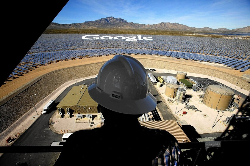 A worker on a tower at the Ivanpah Solar Electric Generating System near the California-Nevada border looks over some of the mirrors tilted to form the Google logo.