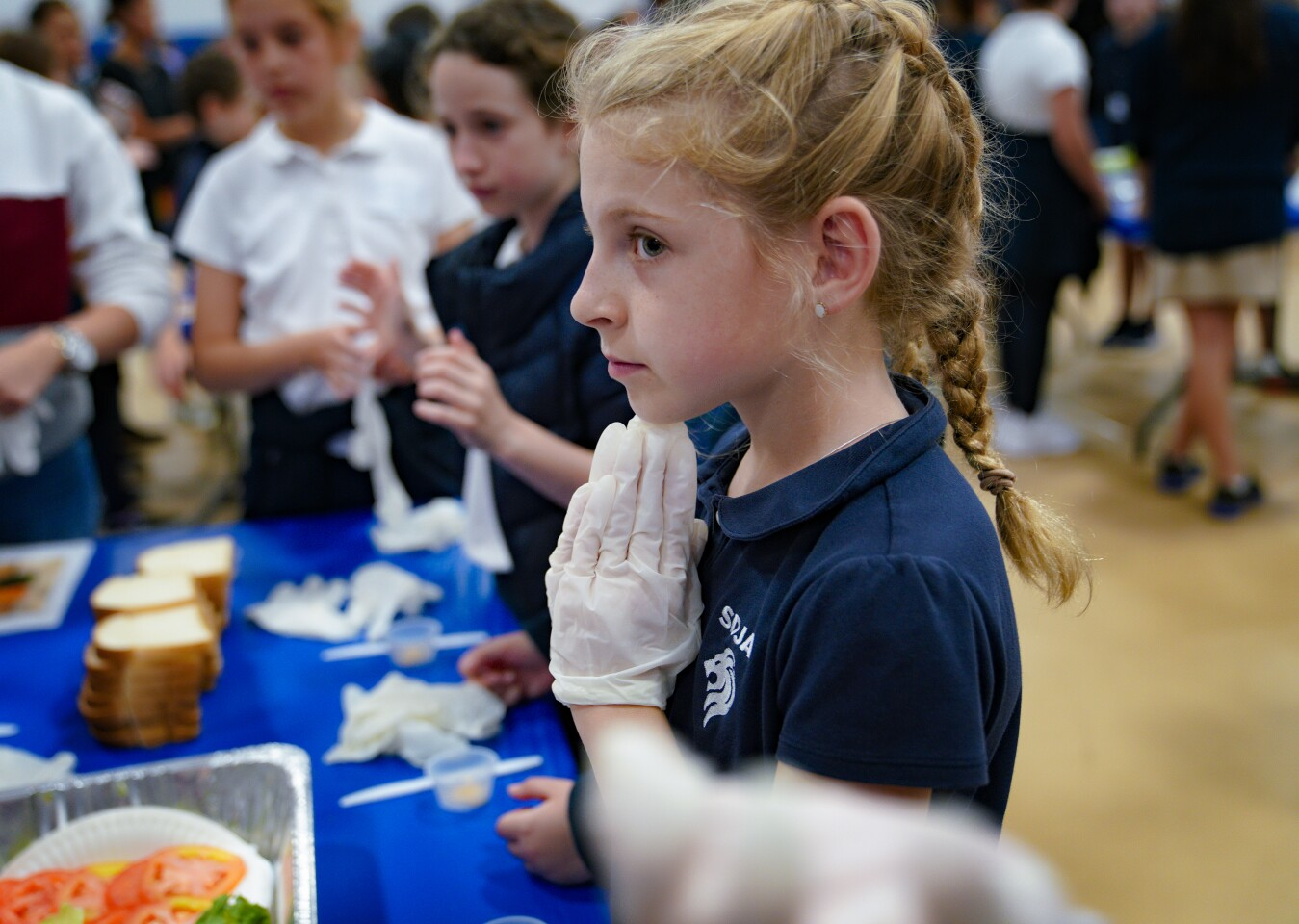 Fourth grader Emuna McCurdy is gloved up and ready for the official start San Diego Jewish Academy's attempt to assembled as many sandwiches possible in 3-minutes.