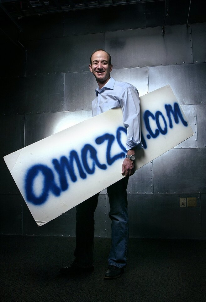 Jeff Bezos, founder, CEO and chairman of Amazon.com, holds the company's first sign, quickly spray-painted prior to an interview with a Japanese television station in 1995, at Amazon's Seattle headquarters.