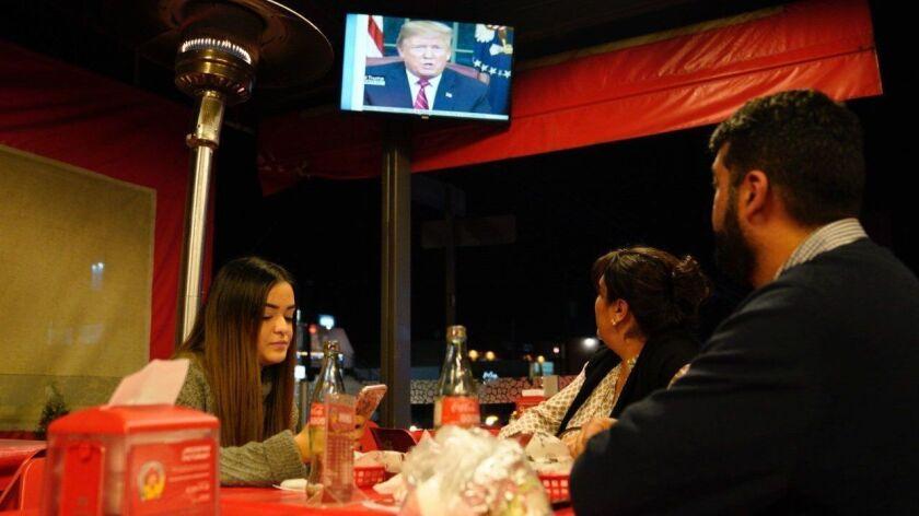Jean-Paul Villalobos (right) and his wife Lilia Villalobos (center) along with their daughter Paola Villalobos from Chula Vista listened to President Donald Trump's speech Tuesday night at the Taconazo restuarant in Tijuana.