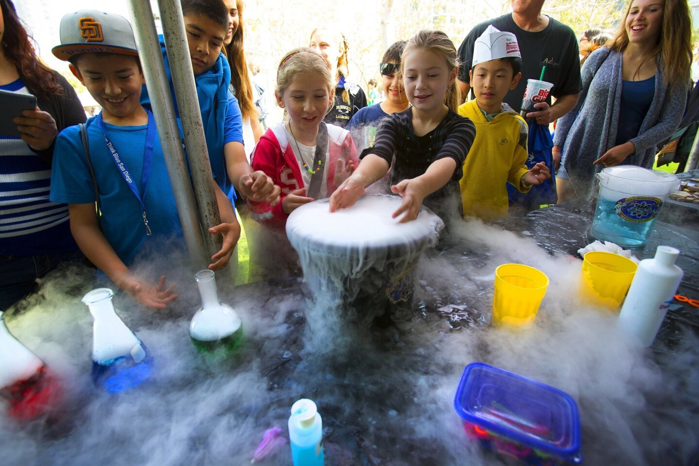 At the Mad Science of San Diego booth, kids watch as the gas produced from dry ice mixed with water begins to spill over during the San Diego Festival of Science & Engineering.
