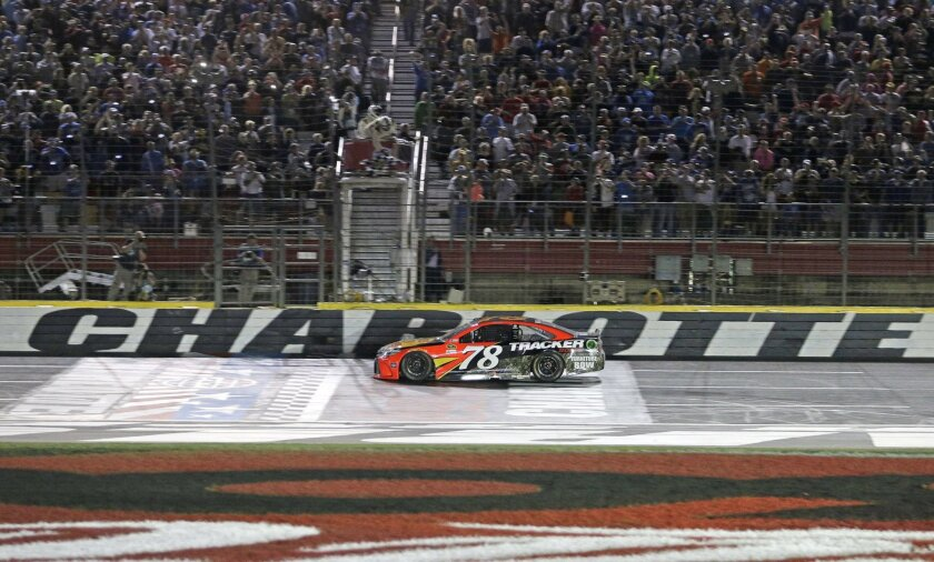Martin Truex Jr takes the checkered flag to win the NASCAR Sprint Cup series auto race at Charlotte Motor Speedway in Concord, N.C., Sunday, May 29, 2016. (AP Photo/Chuck Burton)