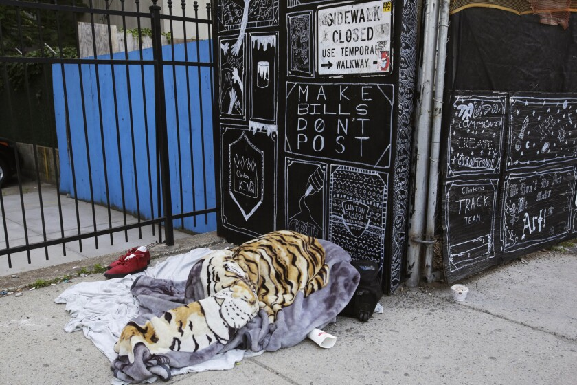 A homeless person sleeps under a blanket on a New York sidewalk.