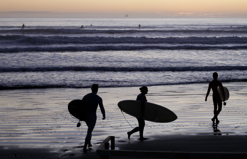 Surfers prepare to enter the water at Sumner Beach in New Zealand