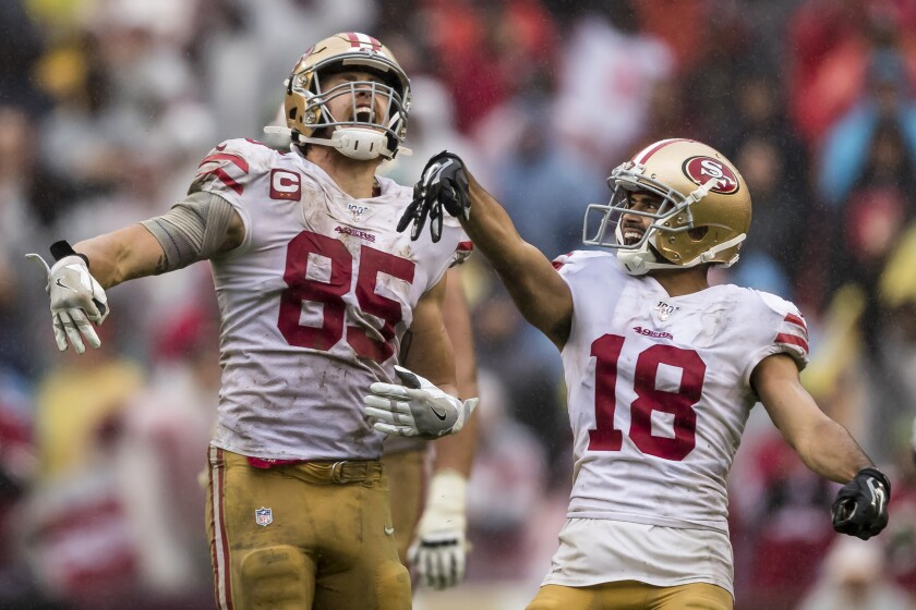 San Francisco 49ers teammates George Kittle, left, and Dante Pettis celebrate after a first down.