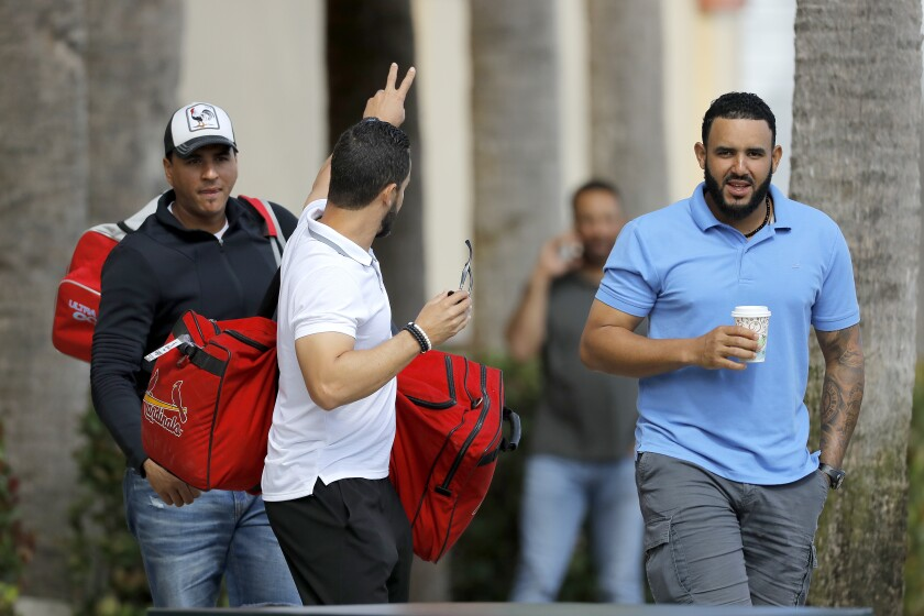 St. Louis Cardinals minor league players leave the team's spring training baseball facility in Jupiter, Fla., on March 13.