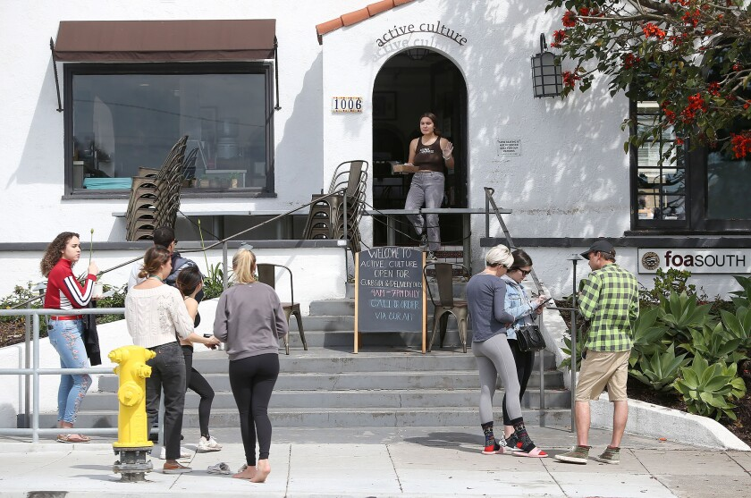 Small groups wait on the sidewalk for phone-in, pick-up orders at Active Culture in Laguna Beach on March 19.
