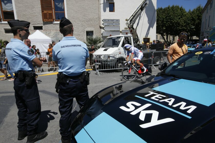 French gendarmes guard one of overall leader Britain's Chris Froome's Sky team's vehicles during the thirteenth stage of the Tour de France cycling race, an individual time trial over 37.5 kilometers (23 miles) with start in Bourg-Saint-Andeol and finish in La Caverne du Pont-d'Arc, France, Friday,