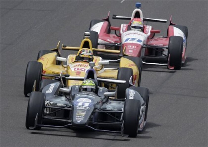 Tony Kanaan, of Brazil, (11) takes the lead from Ryan Hunter-Reay(1) on the 197th lap on his way winning the Indianapolis 500 auto race at the Indianapolis Motor Speedway in Indianapolis, Sunday, May 26, 2013. Justin Wilson (19), of England, finished fifth. (AP Photo/AJ Mast)