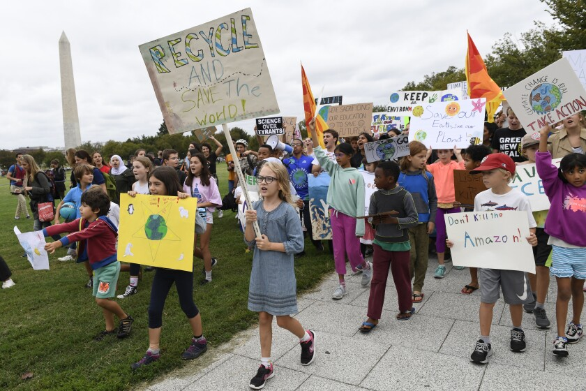 young climate activists march with signs during a rally near the White House in Washington