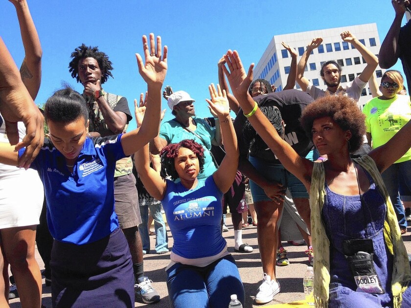 Demonstrators facing a line of police guarding the St. Louis County prosecutor's office in Clayton, Mo., put their hands up, as 18-year-old Michael Brown reportedly did when he was shot dead by a police officer.